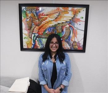 Employee standing in front of a picture frame in office.