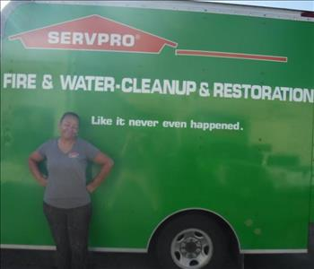 Employee standing in front of a SERVPRO green truck.